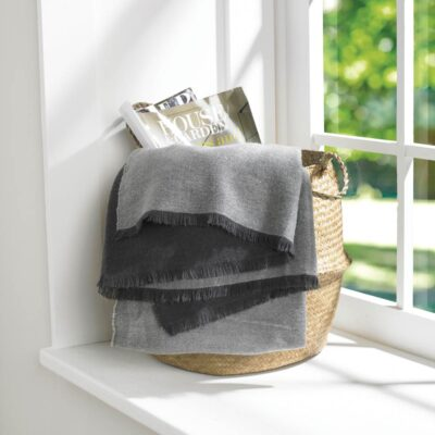 Reversible throw woven in charcoal and grey finished with a fringed edge.