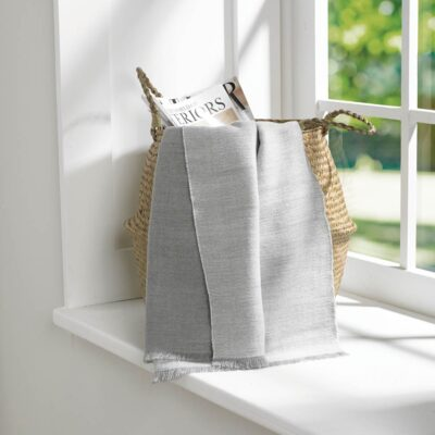 Reversible throw woven in two tones of pale grey finished with a fringed edge